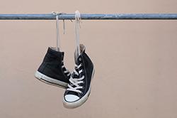 Black sneakers hanging on metal bar